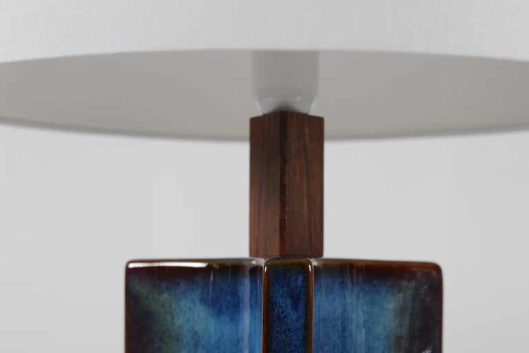 Tall and are sculptural table lamp from Søholm Stentøj, Denmark, circa 1960s. The lamp has glaze with a beautiful color play in almost blue notes.  Included is a new lamp shade designed and made in Denmark. It's made of woven fabric with some