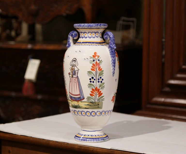 This antique ceramic vase was created in Brittany, circa 1920. Round in shape, the faience piece has curved handles and features colorful hand-painted decor. The painted elements include a Breton woman dressed in traditional, historically accurate
