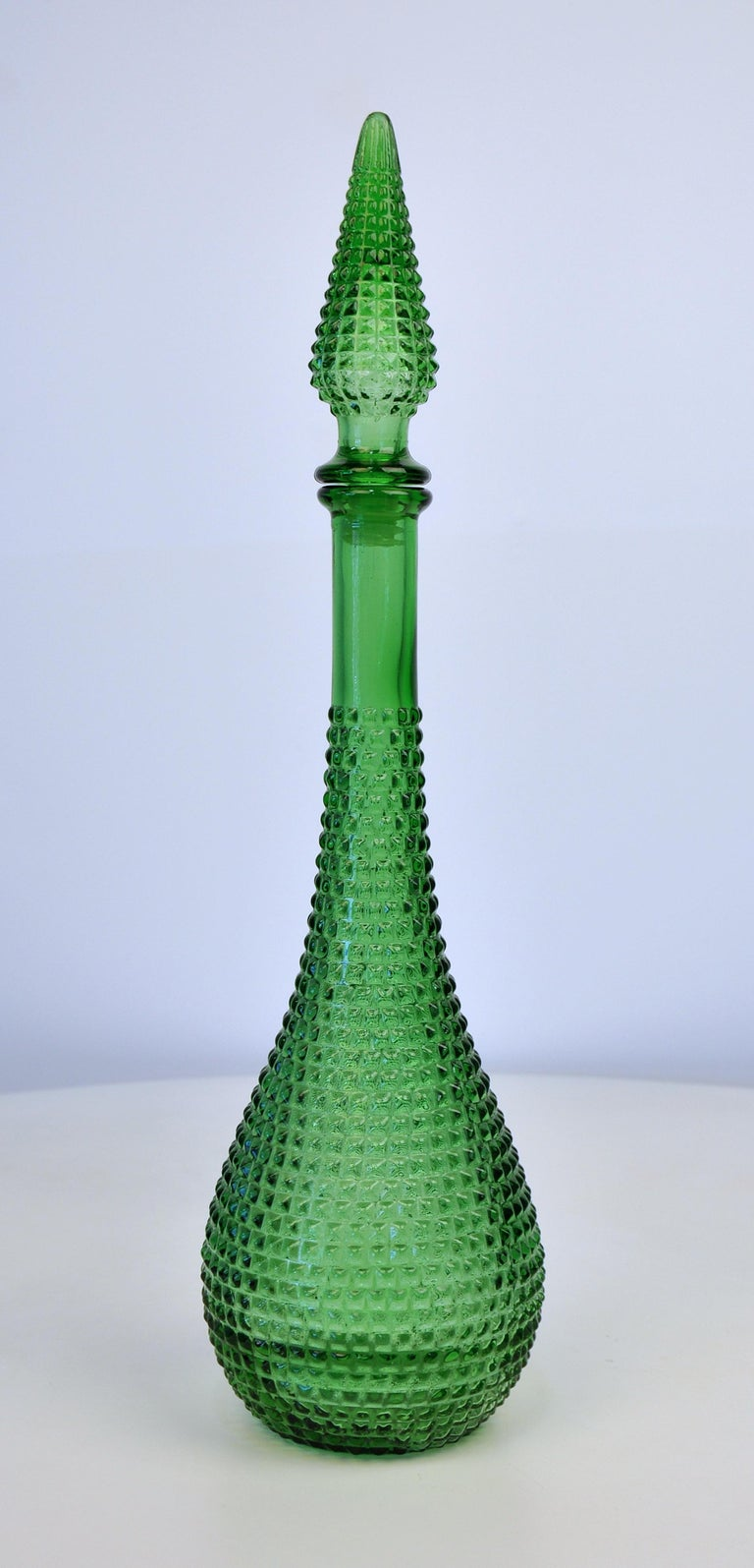 This vintage Italian Mid-Century Modern large art glass genie bottle features a diamond pattern and a rich moss green color. Manufactured by Rossini, it dates from the 1960s. Quite tall and very decorative! Marked Made in Italy on the bottom.