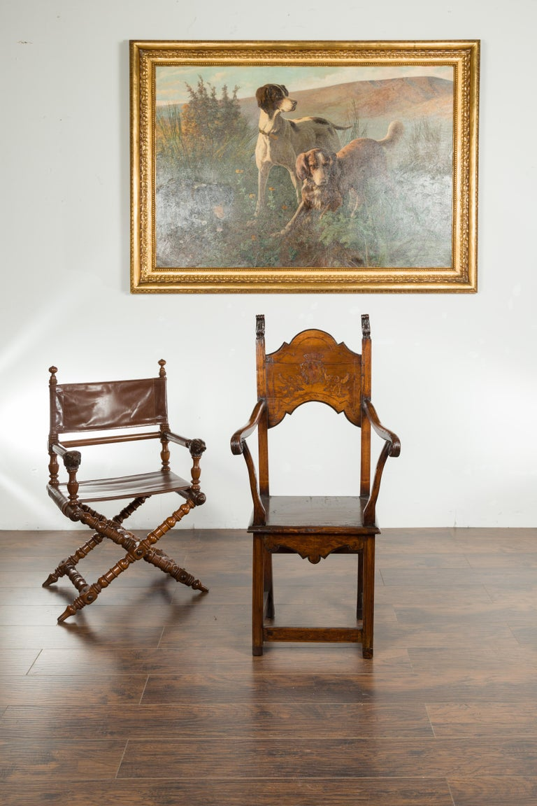 An English Georgian period tall wooden chair from the early 19th century, with carved cartouche and scrolling arms. Created in England during the first quarter of the 19th century, this wooden chair charms us with its tall back, carved with foliage
