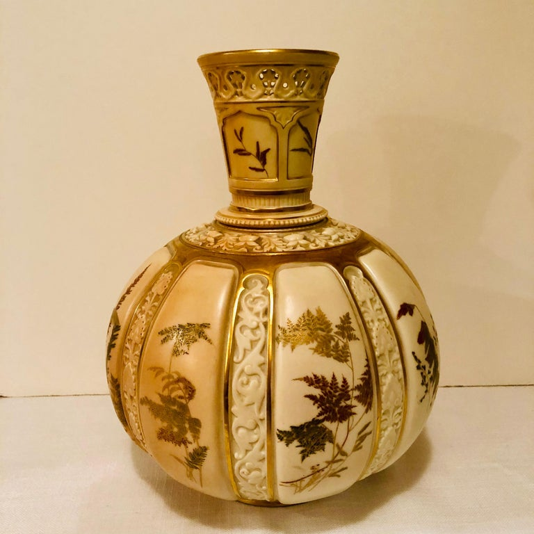 This is a stunning tall Royal Worcester vase hand painted with beautiful ferns and other flora. Each of the flora paintings have raised blush ivory porcelain decoration between them. The top of this vase has openwork detail. It has a bulbous shape