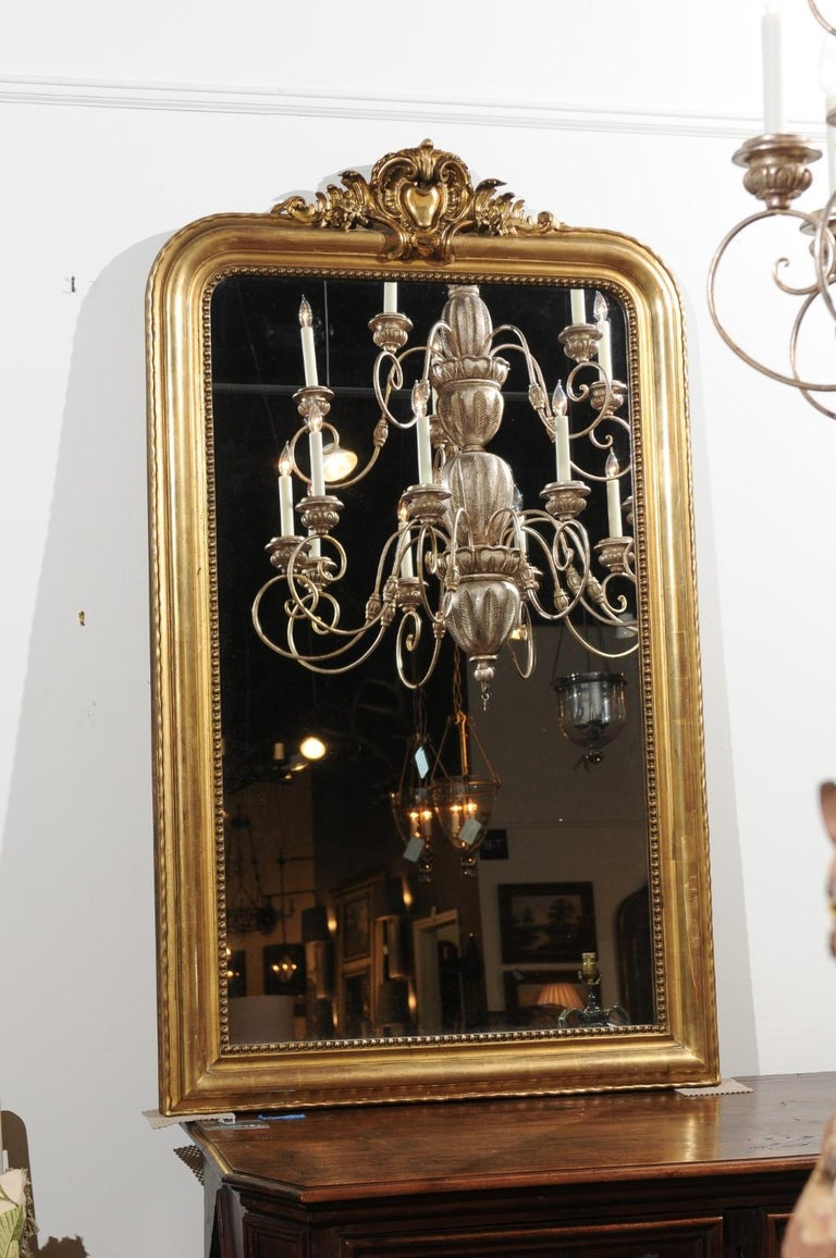 A French tall giltwood Louis-Philippe style mirror from the 19th century with hand-carved crest, beaded motifs and wavy pattern. This French Louis-Philippe style gilded mirror captures all of our attention with its exquisite hand-carved crest,