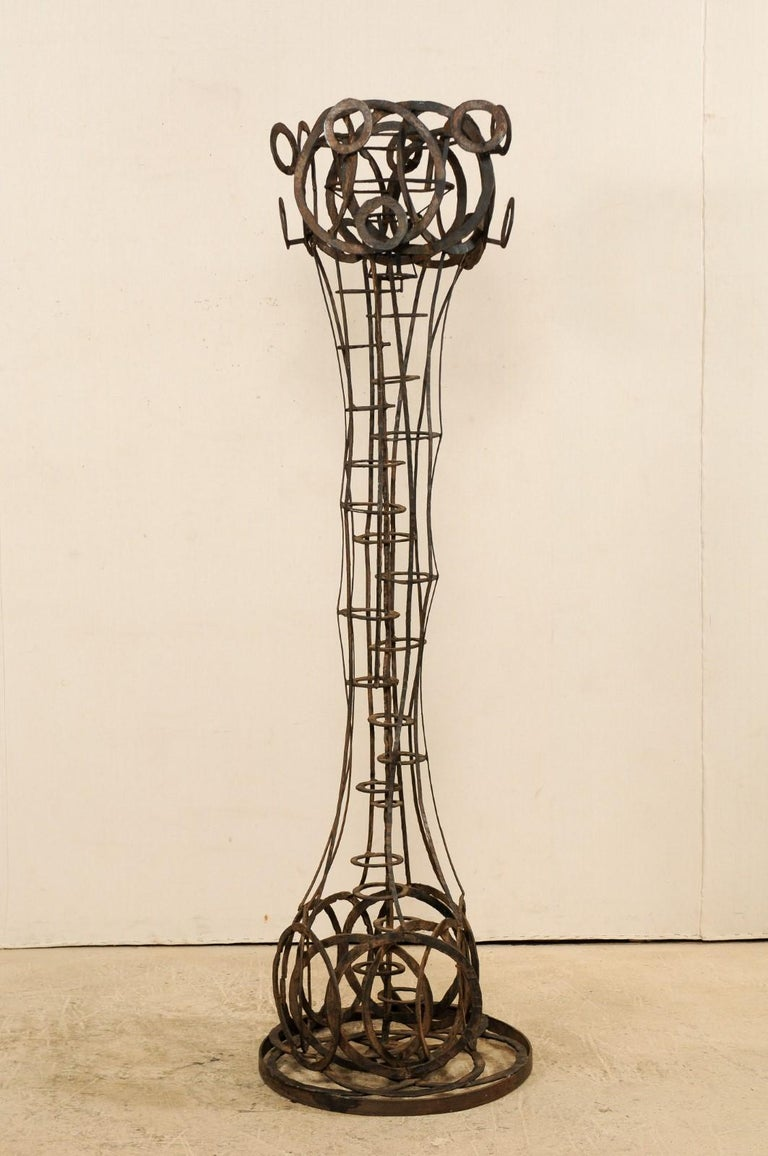 A tall French sculptural iron art piece in a motif of rings from the 1930s-1940s. This unique sculpture from France, standing at approximately 6.6 feet in height, has a playful abstract vertical form made up of a series of rings, with circles
