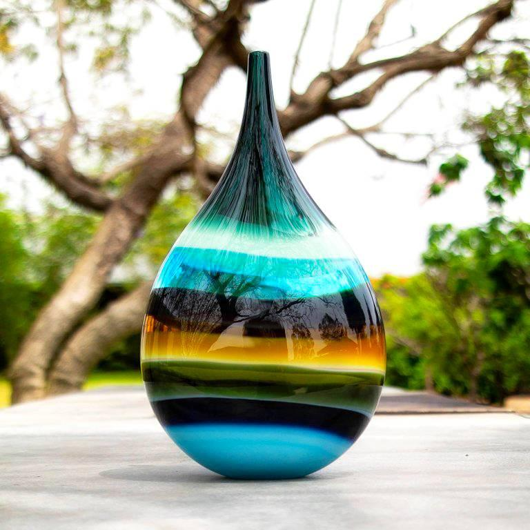 This hand blown glass vase draws inspiration from the rich hues and undulating topography of Southern California. Alternating layers of opaque and transparent colors are applied to clear glass to create a Scandinavian Modern style. Overlaps create