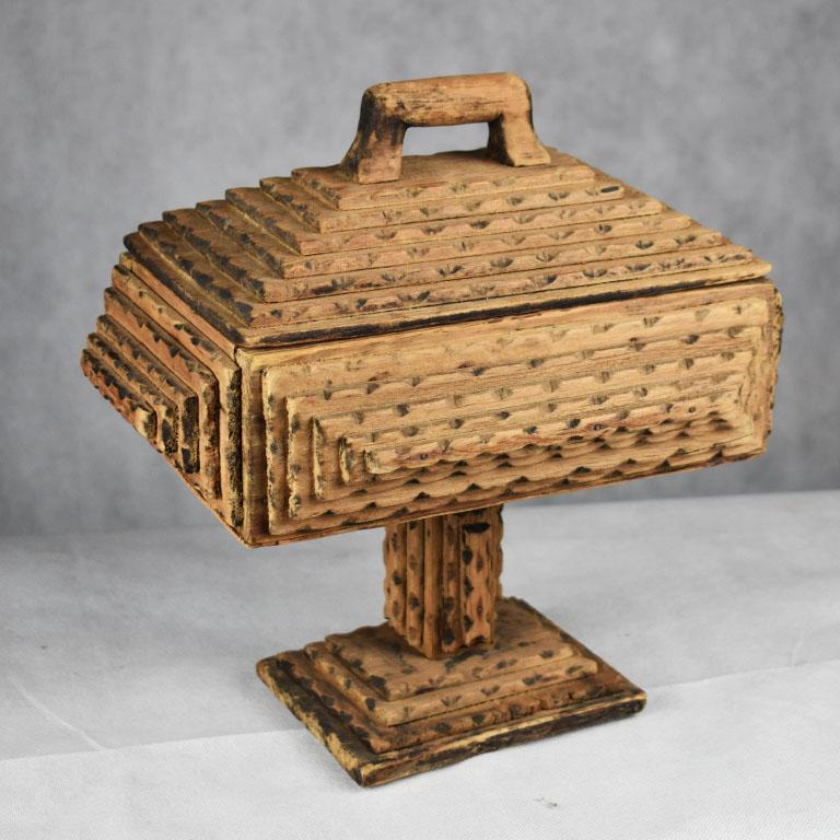 """Often known as """"prison art"""" the most widely acknowledged term for this lovely carved wood piece of Folk Art is know as """"Tramp Art"""". This particular piece is tall and rectangular in shape and sits upon a pedestal base. The top has a removable lid"""
