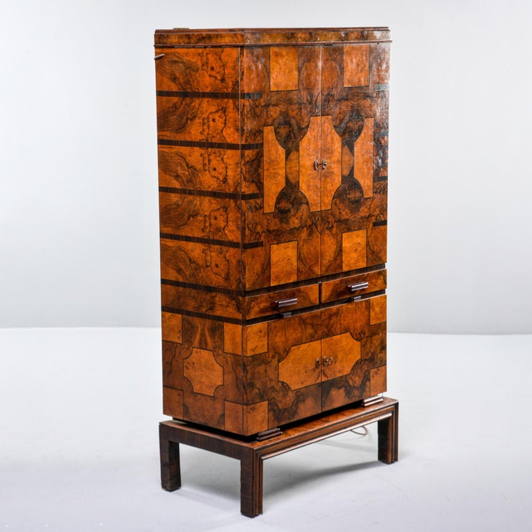 Tall Italian Art Deco bar cabinet features a footed base with locking upper and lower compartments, circa 1930s. Top compartment features 12 stemware holders on the inside of each door, two interior lights, a mirrored back, a removable tray, two