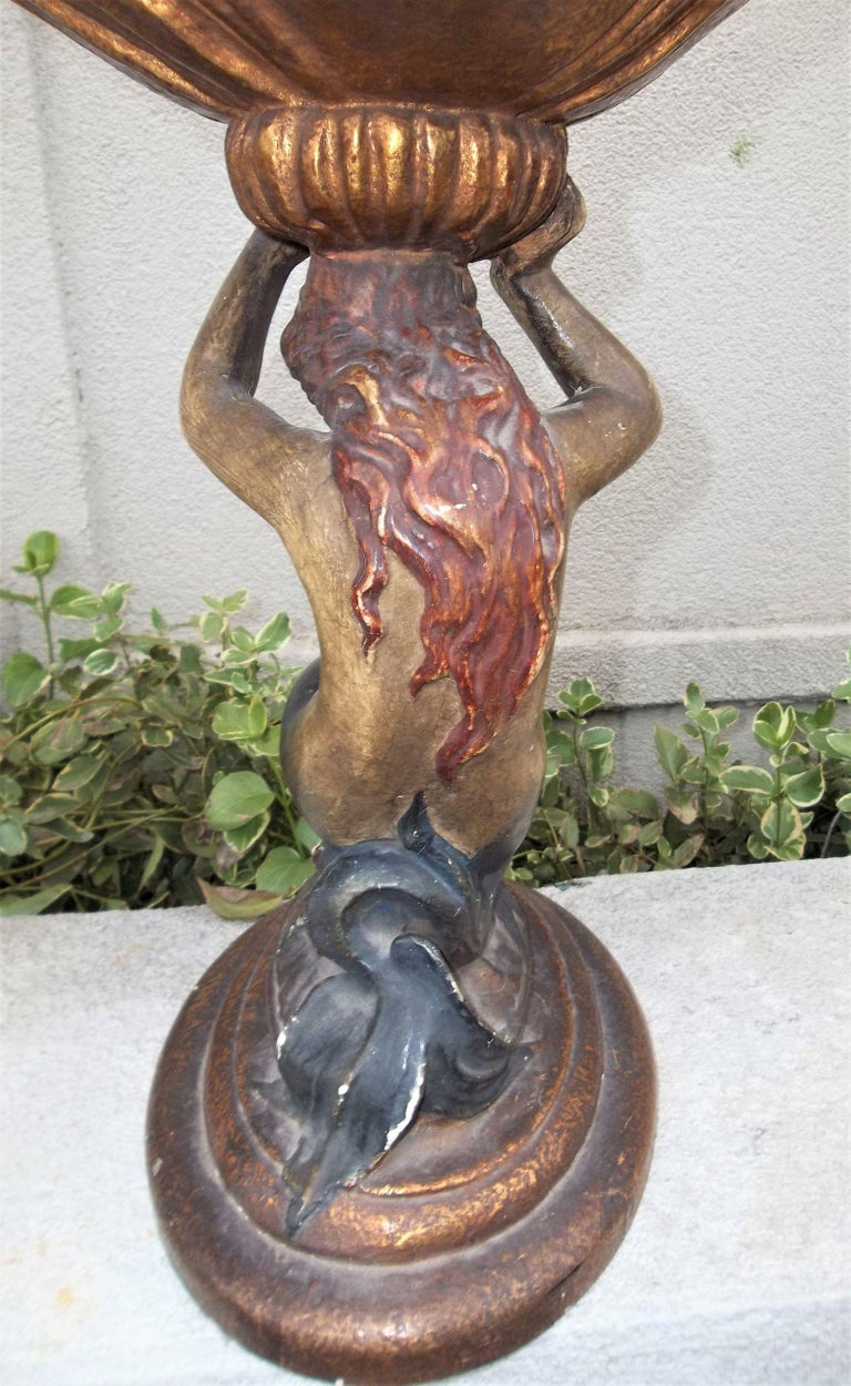 Red haired Mermaid supporting a gilt shell with shallow well. Probably earthenware or chalkware. Sturdy. Some rubbing in places to the paint finish. Dirt, grime and dust of ages. Minor cracks to shell inside. Unmarked but most probably Italian.