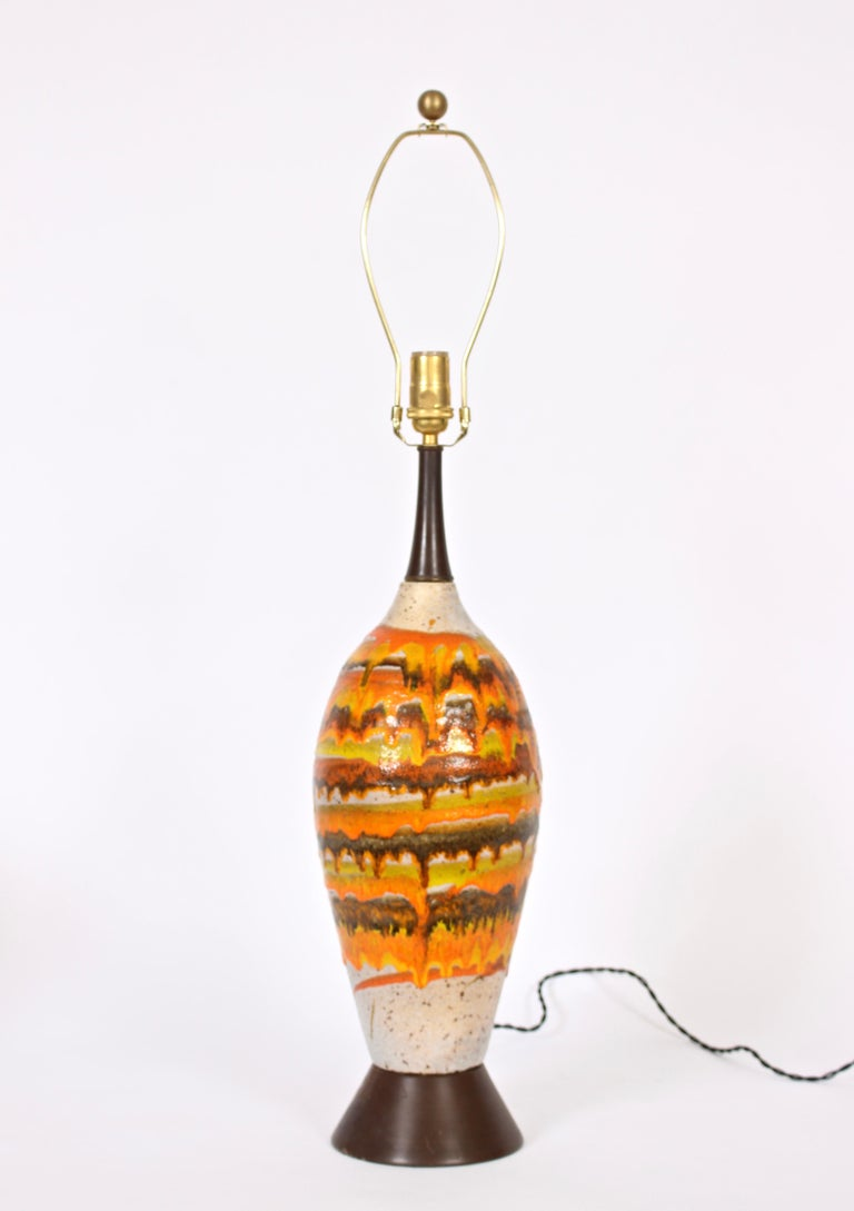 Majestic European crafted ceramic table lamp with vibrant lava banding and drip glazes. Hand painted salt and pepper enhanced natural toned base with orange, gold, mustard, coffee, Chocolate coloration. Brown enameled metal base and neck. Measures: