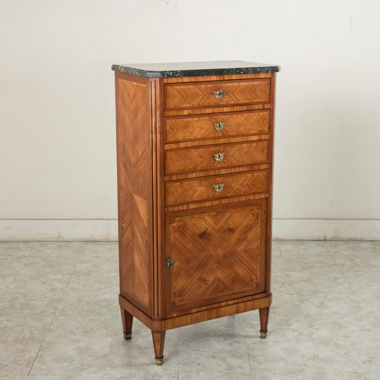 Standing at 48.5 inches in height, this late 19th century French Louis XVI style chiffonier or tall chest features a rosewood Marquetry facade and a Saint Anne marble top. The cabinet has fluted Marquetry corners of rosewood and ebonized pear wood