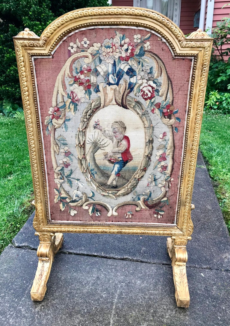Tapestry, possibly Aubusson, probably 18th century fragment set in an 1830 carved giltwood frame. Boy picking flowers.  Back with Christies (Paris) sticker.Christies sold lot info with description and final sale price ( approx. $2049 in 2004 ).  The