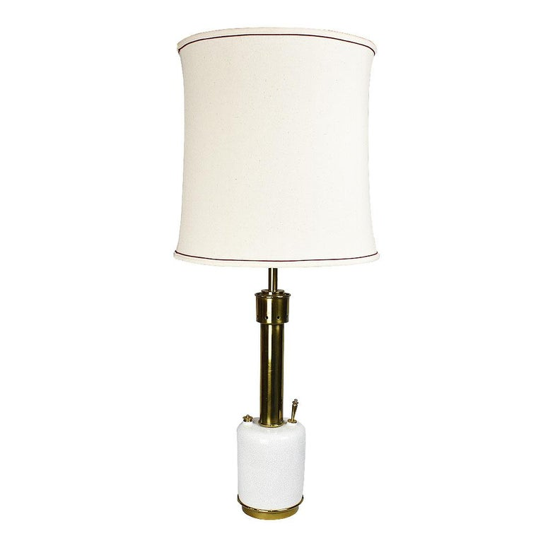 A tall ceramic and brass torchère style table lamp by Stiffel. A rare find, this circular lamp with white crackle glaze, has long been a difficult find for Stiffel lovers. 
