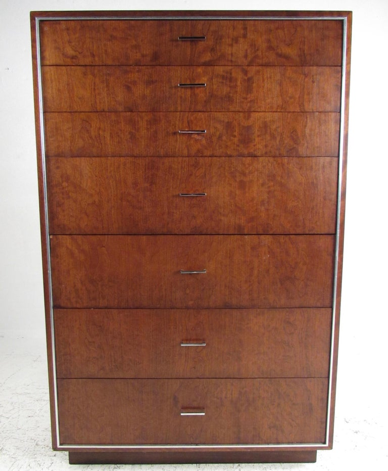 This tall midcentury dresser by John Stuart Inc. features warm walnut tones accented by aluminium trim and chrome drawer pulls. This substantial mid-century highboy makes an impressive dresser in any bedroom setting, offering seven graduated drawers