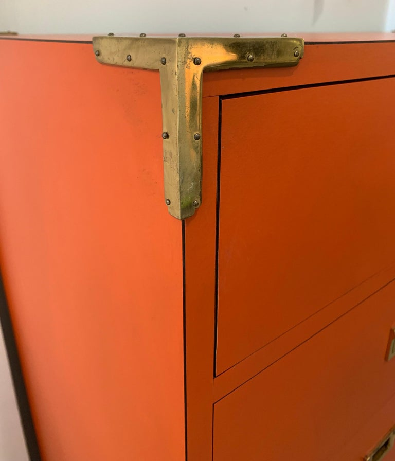 Not easy to find a dresser/highboy with twelve drawers. This one is done in the coveted Hermes orange color with brass hardware and that campaign style look that is always hard to find. Your search is now over. This is the very last piece of this