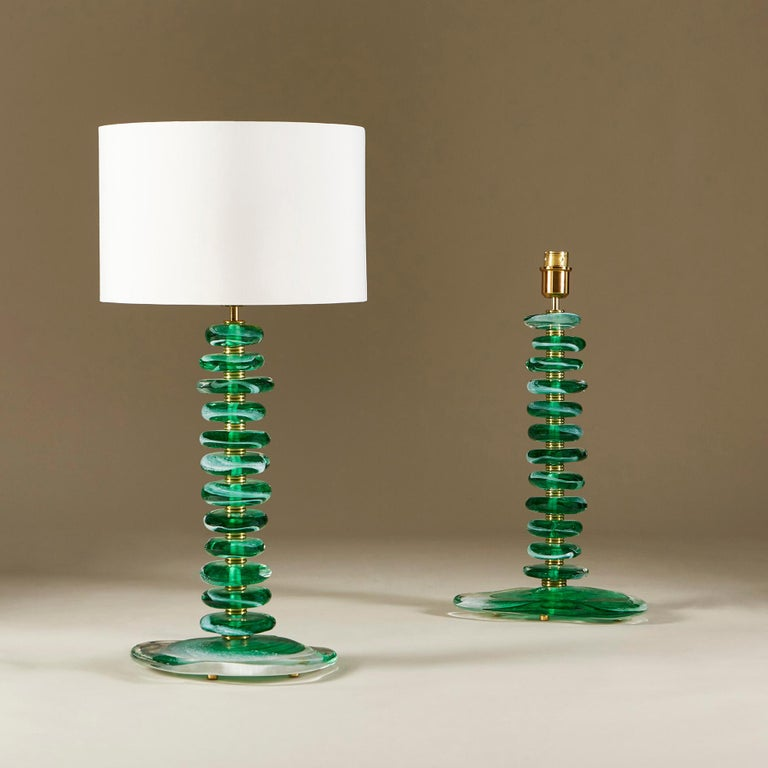 Substantial pair of contemporary table lamps. Each lamp consists of 12 handmade smooth sculptured pebbles in emerald green with clear and white detail. Each pebble is interspersed with double ribbed sections of brass and a brass lamp fitting. Sits