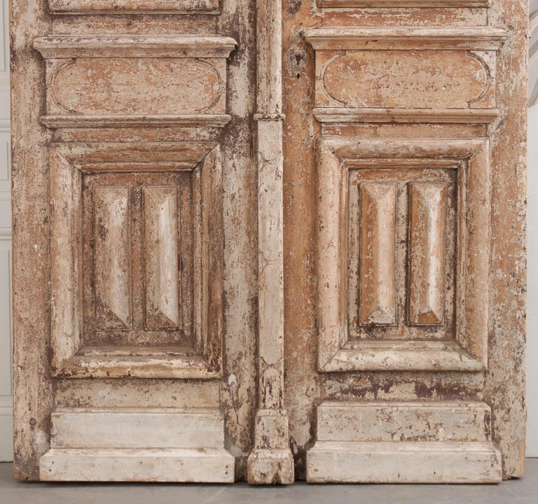 This tall and imposing pair of Napoleon III-style painted-pine and wrought iron entry doors are from France, circa 1900s, and retain the original richly patinated cream-colored paint. Each deeply carved and paneled door is outfitted with restored
