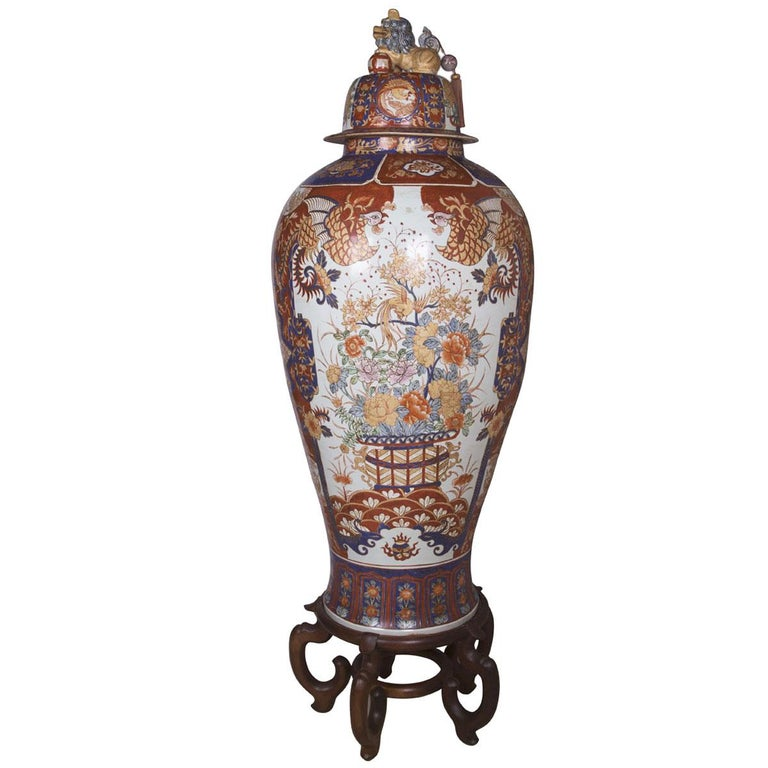 This hand painted tall Imari style vase is made of porcelain. The removable porcelian lid at the top features Fu Dog which is a strong feng shui protection symbol. Wooden stand is includes for this item. This vase measures 66 inches in height and
