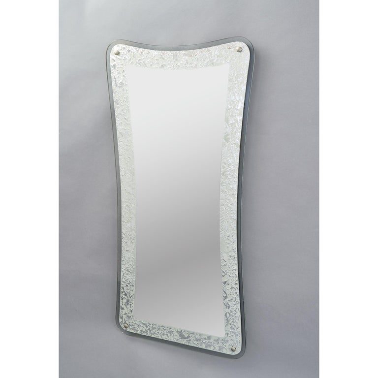 Italy, 1950s Tall shaped mirror with textured silver foil ornemental border Measures: 47 H x 22 W x 1 D.