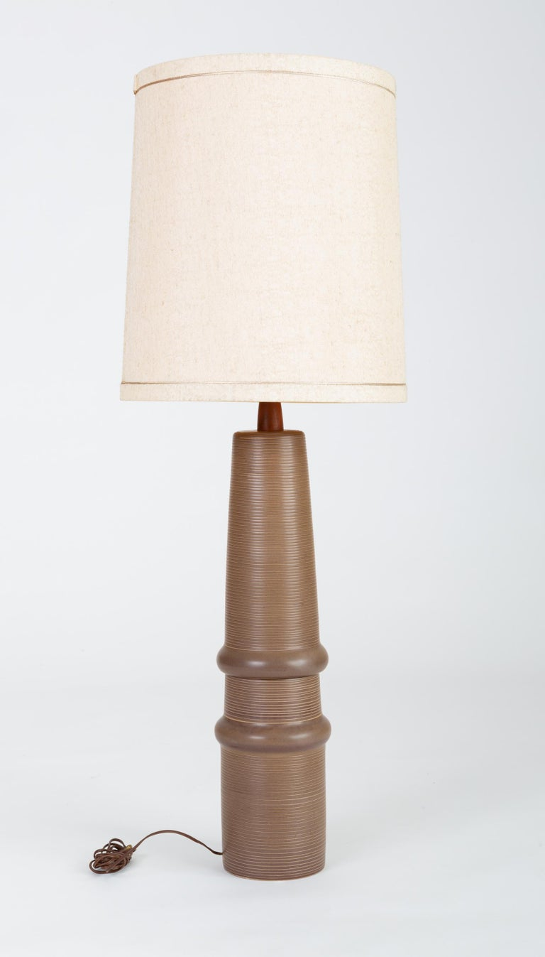 A tall ceramic lamp by husband-and-wife design team Gordon and Jane Martz. Produced by their family company, Marshall Studios in Indiana beginning in 1957, the Model 172 lamp has an organic form with a ribbed texture produced by horizontal incising,