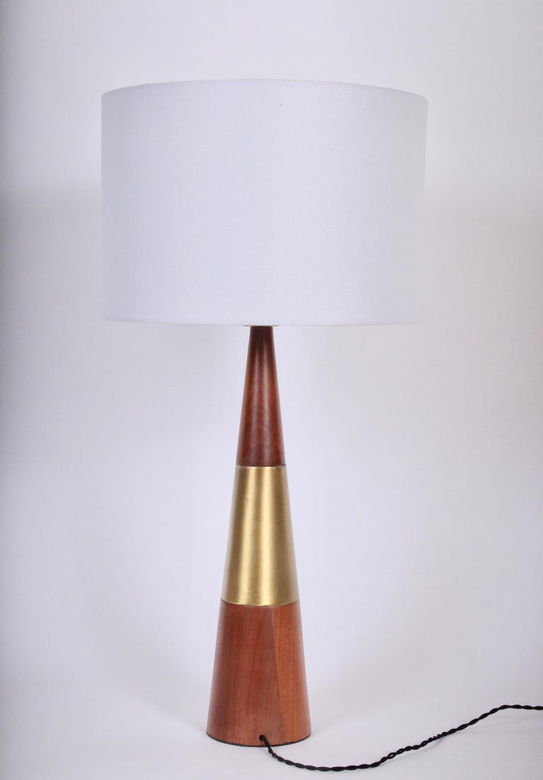 Tony Paul for Westwood Industries Cone Table Lamp in Swedish Brass & Solid Walnut. Circa 1960.  Featuring a sleek conical form in walnut and reflective brass. 21H to top of socket. Small footprint. Shade shown for display only (9.5 H x 14 D).
