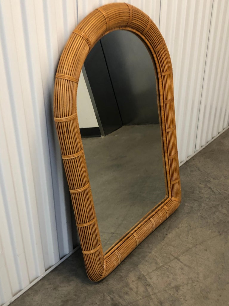 Tall vintage reeded wicker wall mirror with original plywood backing. Oval top and rounded top frame. Hanging hooks in the back. Size: 41.5