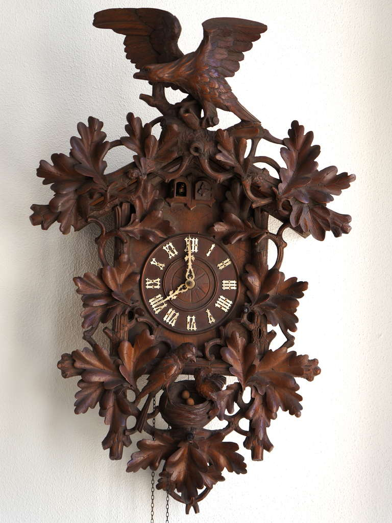 Carved extensively with oak leaves, an eagle with stretched wings on top, a cuckoo sitting on its adoptive parents nest in the bottom, with two cuckoos appearing alternatingly from a double door.