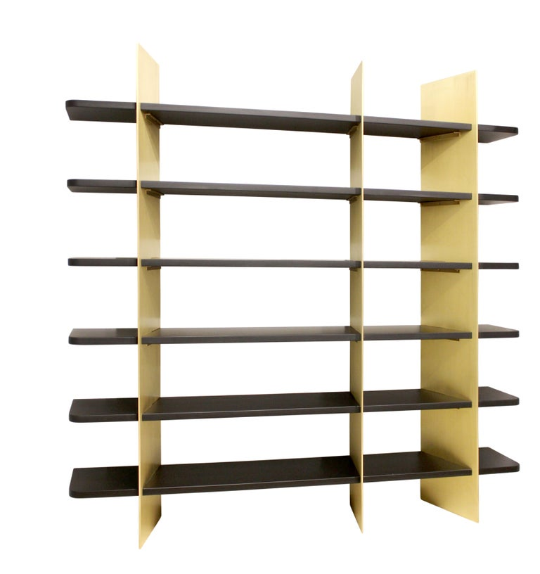 Dramatic brass and matte lacquered wood bookcase. Slotted wood and metal components fit together to form a shelving unit of striking contrast. Custom sizes, materials, and finishes available.