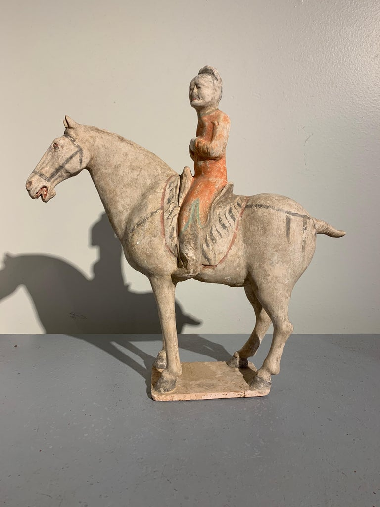 A wonderfully modeled painted pottery figure of horse and rider, Tang Dynasty (618-906 AD), circa 9th century, China. TL tested by Oxford Authentication.  A Classic representation of a Tang Dynasty horse and rider, both figures expressive, with