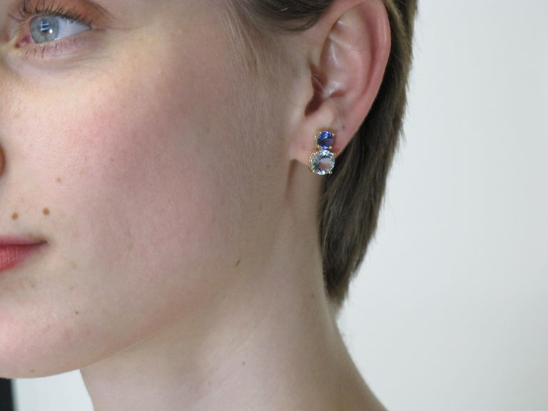 Drink in these stunning earrings inspired by the ocean! Two vibrant Aquamarines,  3.06 carats total weight, are combined with two gorgeous Tanzanites,  1.48 carats total weight, to make these earrings a wonder to behold. Handmade with care by our