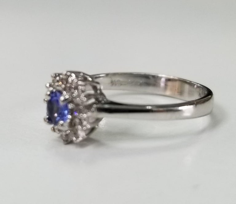 14k white gold Tanzanite and diamond cluster ring, containing 1 round tanzanite weighing .15pts. and 12 round full cut diamonds of very fine quality weighing .12pts.  This ring is a size 4.5 but we will size to fit for free.