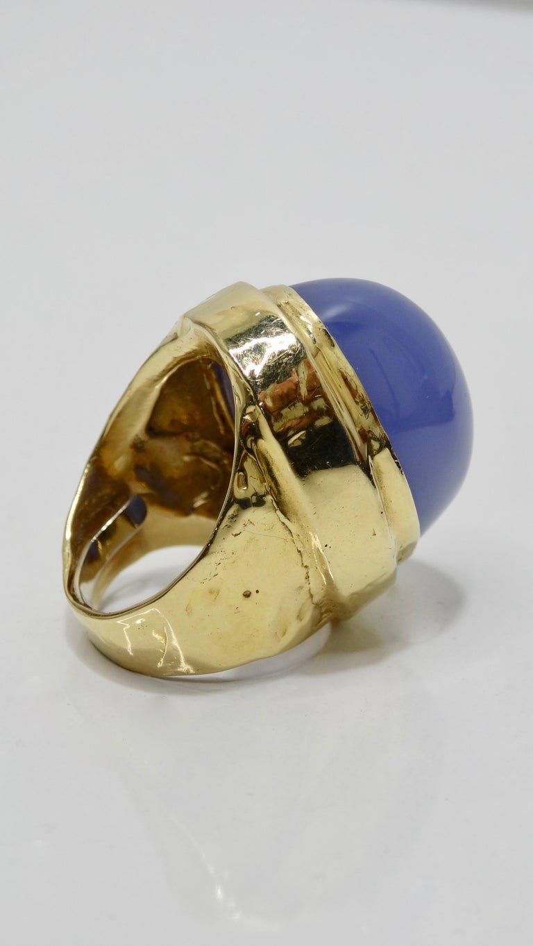 Show off with this stunning cocktail ring! Circa 1970s, this 14k Yellow Gold cocktail ring features a slightly textured band set with a large Cabochon Tanzanite gemstone (approx. 15ct). Weighs 28.38g total and is made to fit a size 6. Modified with