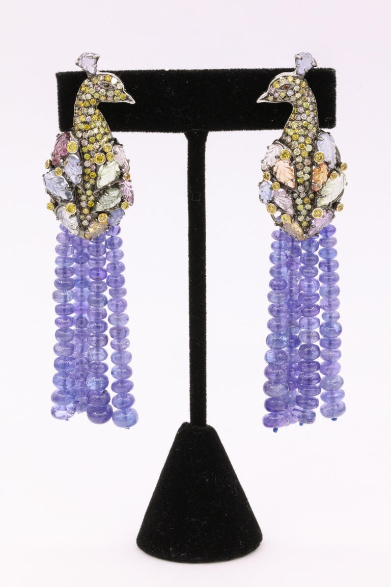 These one of a kind earrings feature a diamond Peacock with multi color diamonds weighing approximately 4 carats and carved color sapphires as wings weighing approximately 22 carats. Extended is a total of 16 tanzanite strands weighing over