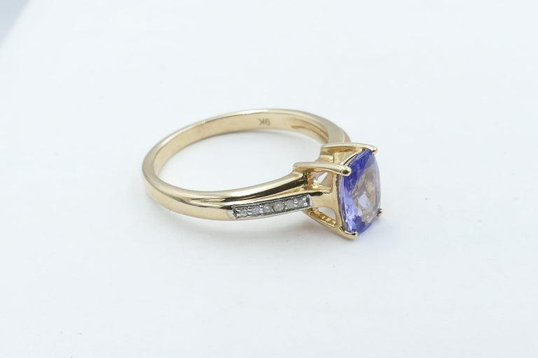 One 1.34 carat Tanzanite with Colour of Purplish-blue, Tone medium, Clarity eye-clean, Rectangular Cushion Cut, 4 claw set, is flanked by 12 Single Round Cut Diamonds J/K Colour Clarity I1-I2 makes up this very versatile Ring that presents as an