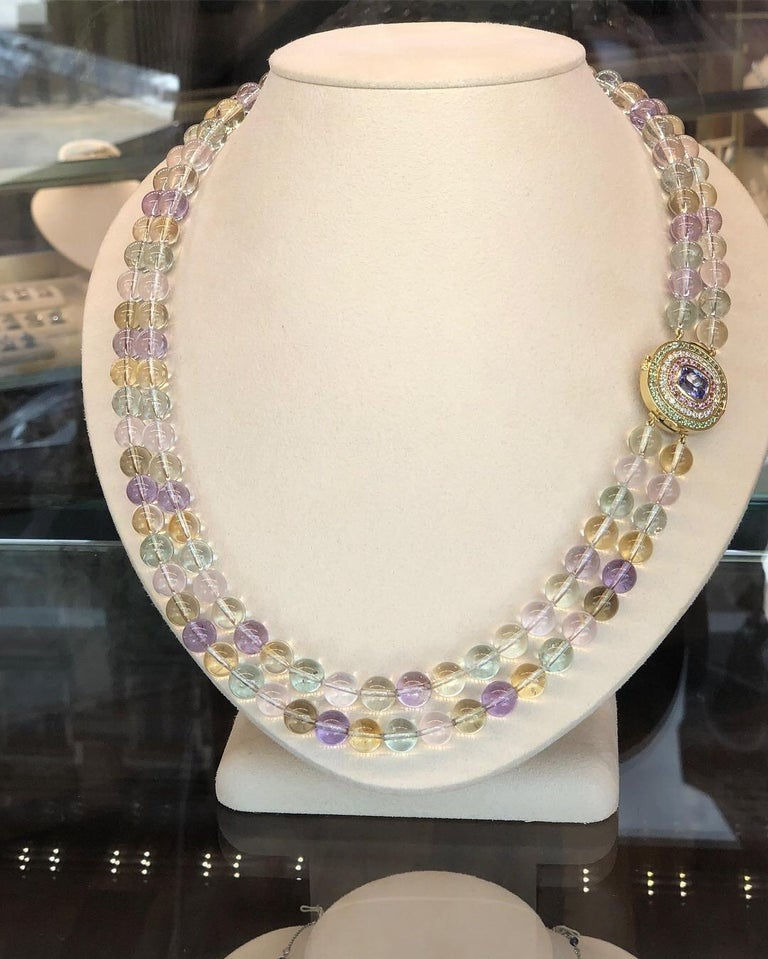 A beautiful necklace made of 921 carats of 10mm natural spodumene beads in a variety of graduated colors. Spodumene is also known more commonly as Kunzite for the pinkish violet variety or Hiddenite for the Green variety. Colors outside of the