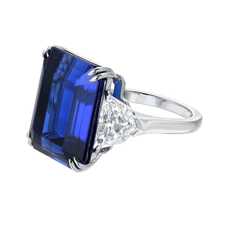 This unmatched 20.51 carat emerald cut Tanzanite, flanked by a pair of 2.04 carats total F/VS2 Diamonds, is hand set in this extraordinary hand crafted platinum ring. The combination of its rich vivid blue hue, strong saturation, complimented by its