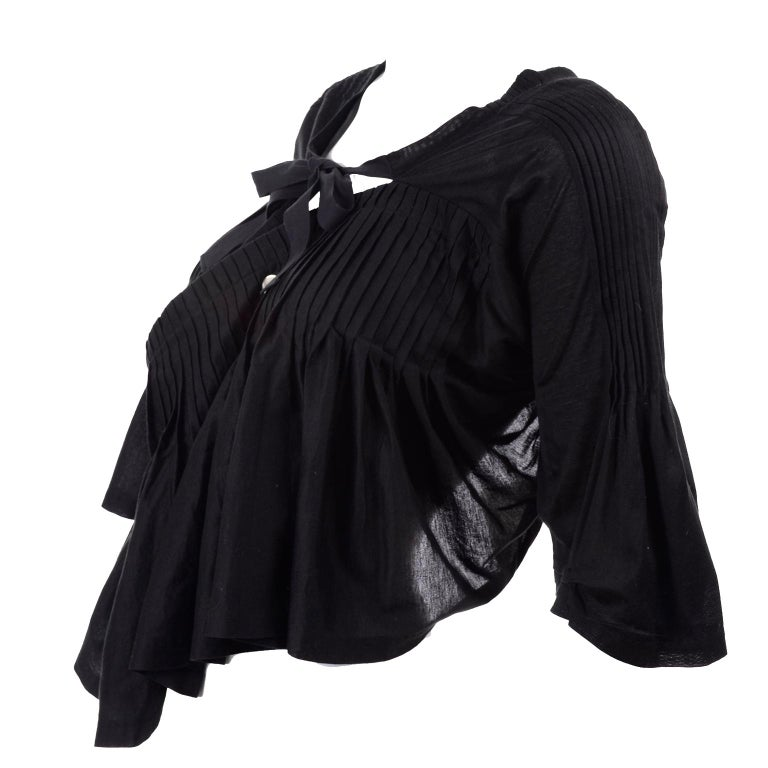 This is a fabulous top from Comme des Garcons with the original $1065 price tag and all other tags still attached . Purchased at Barney's, this avant garde top has an open back, beautiful pleats & tucks, and is in a poncho style with 3/4 length