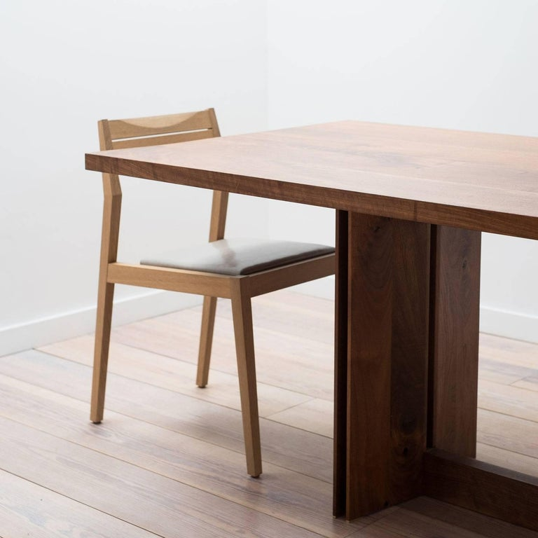 A rectangular dining table that showcases the quality and beauty of each hand selected board of wood. The base of the table pairs strikingly thin edges with negative space creating a strong, yet light appearance.