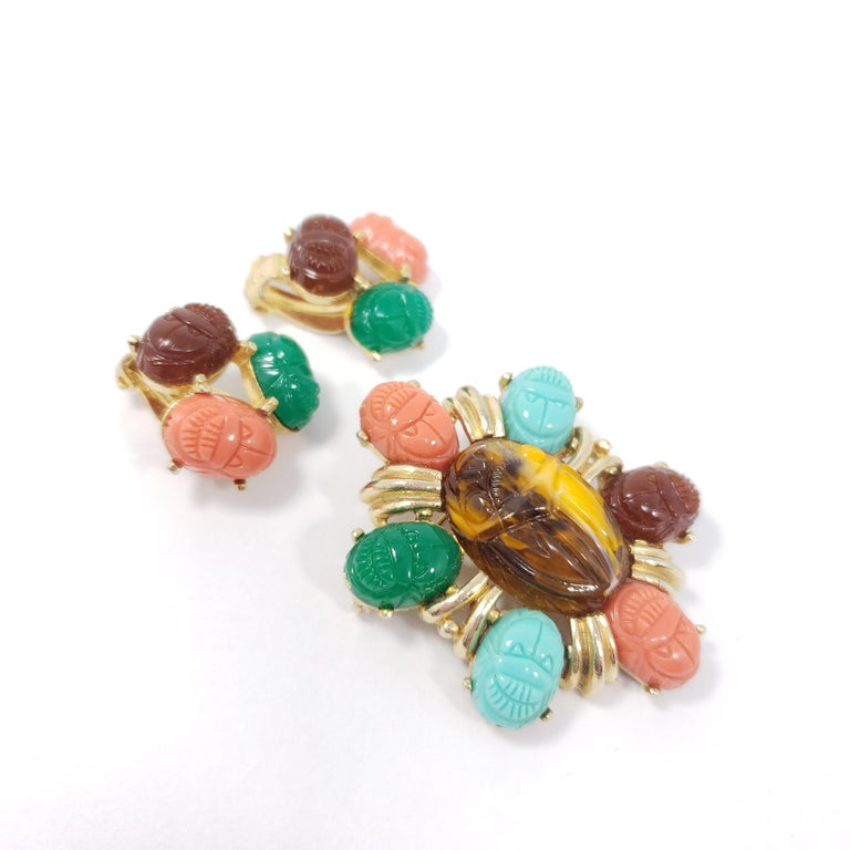 A colorful pin brooch and clip-on earring set by Tara, a mid-1900s costume jewelry designer. Each piece features colorful carved resin scarabs prong-set in a gold-tone metal setting. DeLizza and Elster are believed to be the original designers