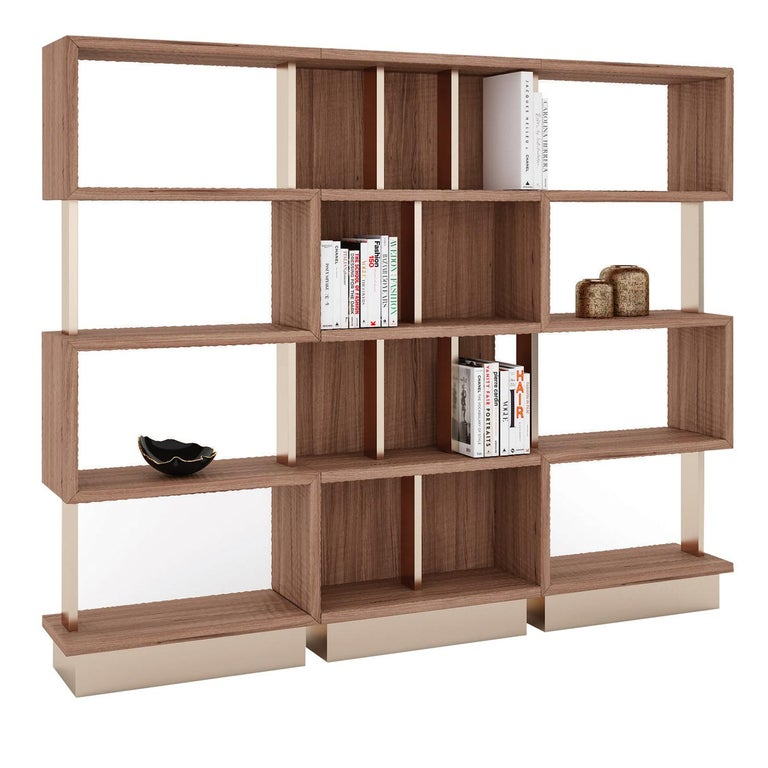 Boasting an elegant allure for its shape and chromatic combination, this wooden bookcase features a white-lacquered structure and stands on a brass-finished metal basement, sharing the same stunning finish of the frame's metal details. Increasing