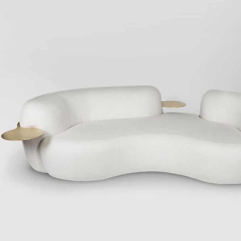 Tateyama is a sculptural sofa featuring soft curves and a unique design. Cozy and comfortable, it is characterized by an opening in the backrest that lightens its structure. The sofa is available with or without built-in tables. Wooden structure