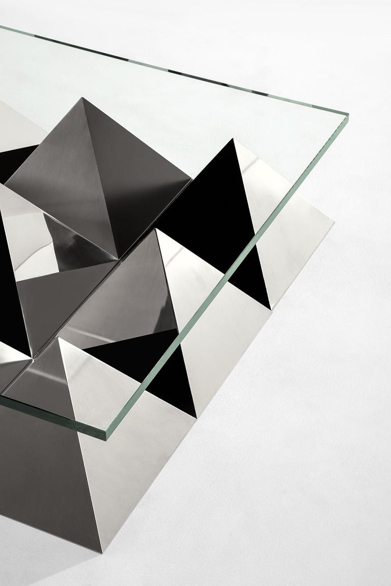 Low table with top in float glass. Base composed of a pyramid in black Marquina marble surrounded by steel pyramids with different faces finishing: black matte paint, satin and polished steel. Progetto Non Finito collection from Dimoremilano,
