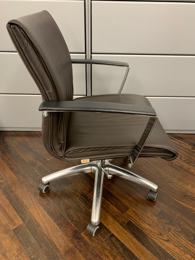 Upholstered in brown leather  on casters Swivel. NEW SET OF CASTERS