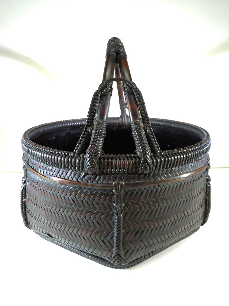 Tea ceremony woven round bamboo basket with handle used for storing charcoal. The inside lining is lacquered. Comes with signed tomobako by artist Tokyusai. His signature is also on the bottom of the basket.