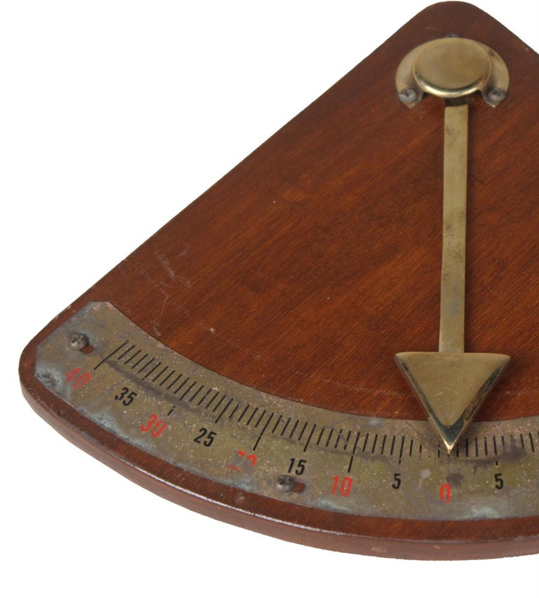 A handsome brass and teak ship's clinometer. Used to measure the degree of healing on a boat, or on larger boats to weigh the distribution of cargo to be sure the ballast is even. Midcentury, European.