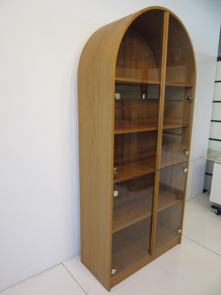 A nice sized domed top bookcase with four shelves not counting the bottom base shelve with back lighting, two upper and two lower glass doors having brass detail hinges. Matching teak trim running on the front door edges forming the handles, retains