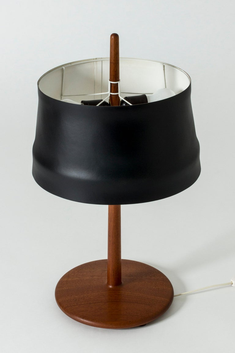 Cool table lamp by Alf Svensson, with a teak base and stem, where the tip of the stem shoots up out of the top of the open shade. Very nice, smooth teak in a streamlined shape. Lacquered black metal shade.