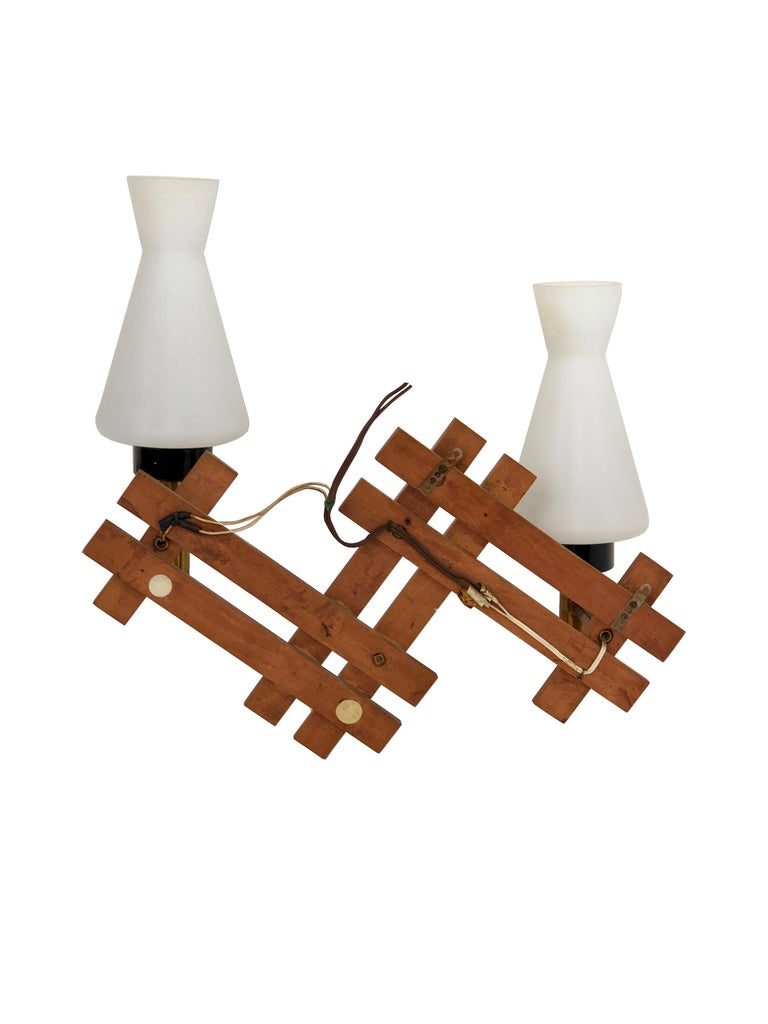 Teak and brass wall sconces featuring two lights in opaline glass, made in Italy during the 1960s.