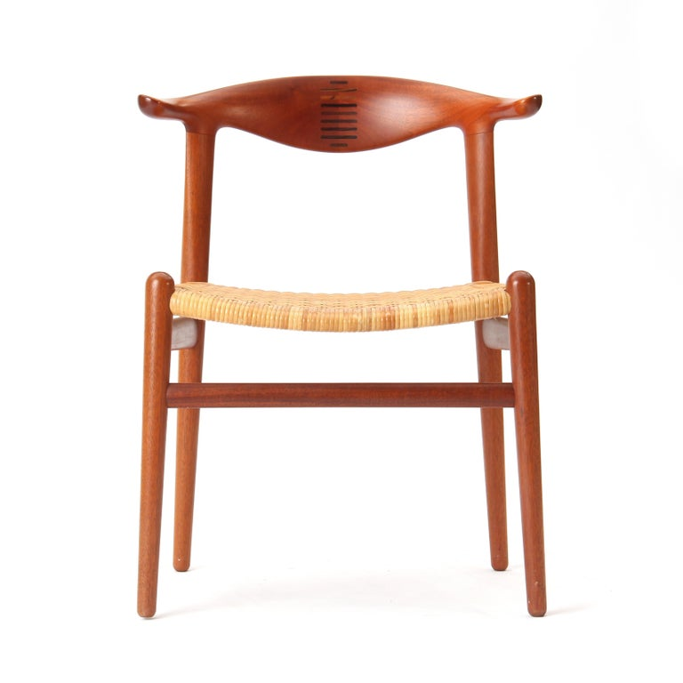 A rare teak Danish modern dining chair with a splined backrest and a natural cane seat. Model JH-505 was designed in 1952 by Hans J. Wegner and produced in the 1960s by Johannes Hansen.