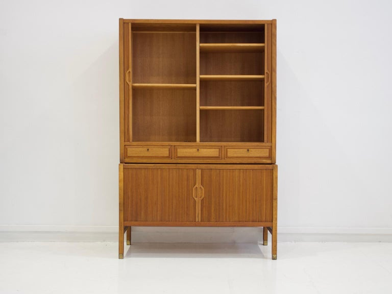 Teak cabinet designed by Carl Axel Acking and manufactured by Bodafors. Consists of two pieces, top and bottom. Front with tambour doors and drawers, interior with shelf, feet with brass shoes, key available.
