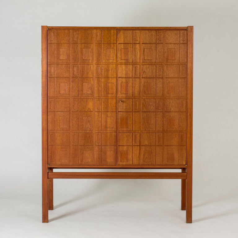 Amazing teak cabinet by Eyvind Beckman, in an elegant, clean design. Graphic relief pattern of cut out rectangles on the front. Practical shelves and drawers inside.
