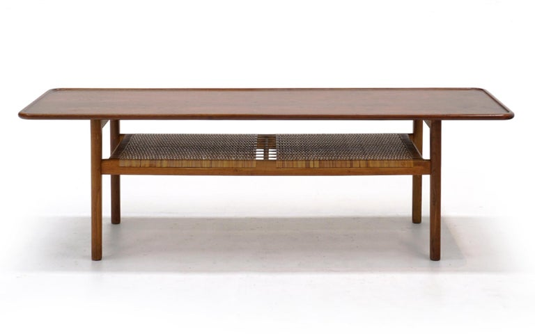 Hans Wegner teak and cane coffee table in completely original condition. Produced by Adreas Tuck, Denmark, 1950s. This is a fine all original example of this design.